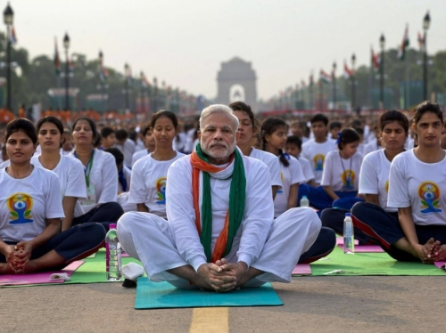 Indian Prime Minister Narendra Modi, center,  sits on a mat as he performs yoga along with thousands of Indians on Rajpath, in New Delhi, India, Sunday, June 21, 2015. Millions of yoga enthusiasts are bending their bodies in complex postures across India as they take part in a mass yoga program to mark the first International Yoga Day.(AP Photo/Saurabh Das)/XSD104/279604393046/1506210625